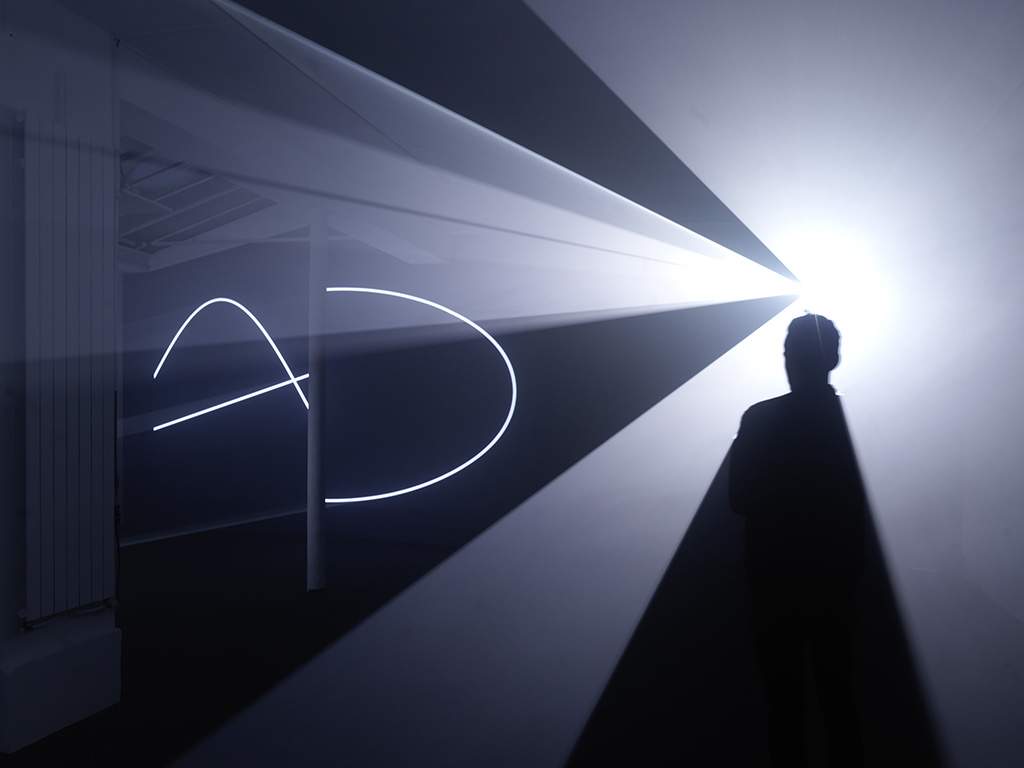 2013, installation (horizontal, double), computer, Quicktime Movie file, two video projectors, two haze machines, one cycle of 24 minutes in two parts, edition of 3 <br> <br> A two-projector, horizontal installation. The two volumetrics forms are positioned alongside one another while the projectors point in opposite directions. Because of this reversal, the observer can study the drawing on the wall while simultaneously occupying the volumetric form produced by it. Face to Face IV is focused on the precise moment when the flat drawing is transformed into space. First Shown at Galerie Martine Aboucaya, France, in 2013.