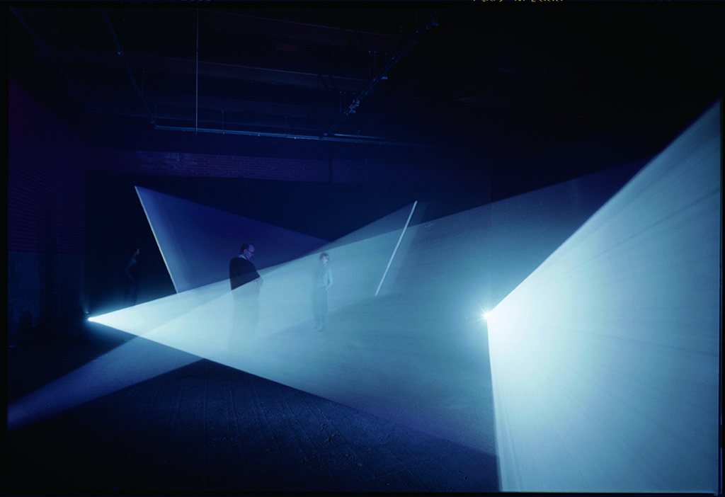 1974, installation, 16 mm film, black-and-white, silent, four projectors, one cycle of 5 hours 30 minutes in eight parts, edition of 3 plus 1 AP <br> <br> A single fifteen-minute sweep of triangular blade of light through 90 degrees, along a wall, becomes four distinct architectural interventions through the agency of the projector.