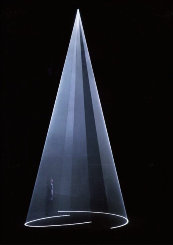 2009, installation (vertical, single), computer, computer script, video projector, haze machine, one cycle of 15 minutes, edition of 5 <br> <br> Single-projector, vertical in orientation, this piece is based on a slow, back-and-forth exchange between two identical elliptical cones, which expand and contract at different speed. These two overlapping forms of motion produce shifting interior volumes of space together with the gradual opening up and closing down of the entry apertures. First shown at Hangar Bicocca, Milan, 2009.