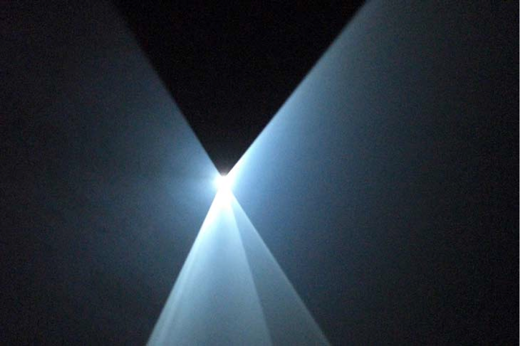 2006, installation (horizontal, single), computer, Quicktime movie file, video projector, haze machine, one cycle of 30 minutes in two parts, edition of 5 plus 1 AP <br> <br> Single projector, horizontal in orientation, this piece is stripped down to an exchange between just two elements; the elliptical cone and a triangular plane which is either a traveling wave becoming flat, or a flat plane becoming a traveling wave. First shown at the Vardy Gallery, Univ. of Sunderland, March 2006.